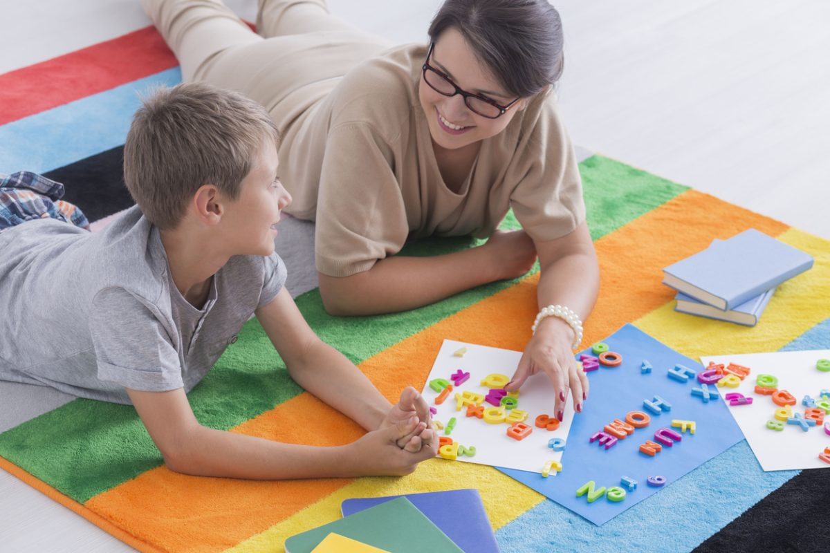 Young woman and kid solving puzzle on floor